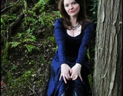 Pale lady in velvet with vampire skin in the twilight woods of Washington